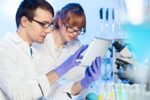 Female and Male pathologist in lab coast looking at a tablet