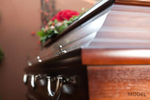 Wooden Casket at Funeral with Red Rose On Top